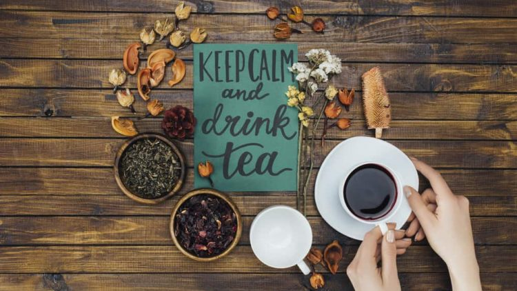 "Wood table with a paper ""Keep Calm and drink tea"" written on paper. Surrounded by cups of tea and herbs."