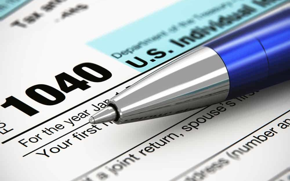 Tax form business financial concept: macro view of individual return tax form and blue metal ballpoint pen